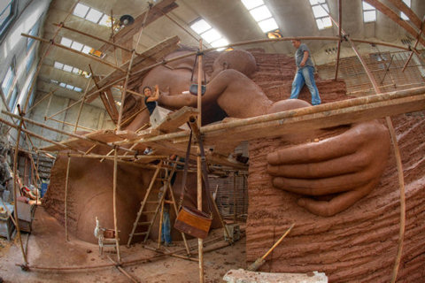An image created by photographer David McBride of Zhang Yaxi's Mother and Child sculpture - showing the sculptor working on her monumental sculpture at the clay stage