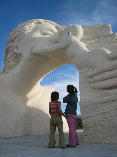 Local children seem dwarfed by the monolithic monumental sculpture of Chinese sculptor Zhang Yaxi